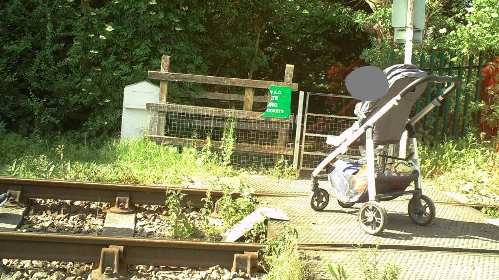 An image of a pram on the railway tracks