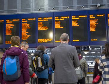 An image of rail passengers staring at a service board at a railway station.